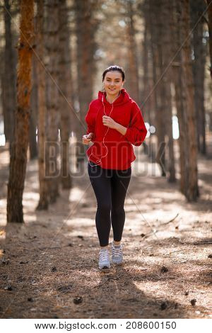 Young brunette athlete in a red sweatshirt is running around in headphones in an autumn forest. Close-up. In full growth. Sport.