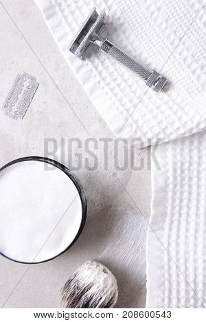 Shaving Still Life: Safety razor with towel, brush and soap and blade on a gray tile surface.