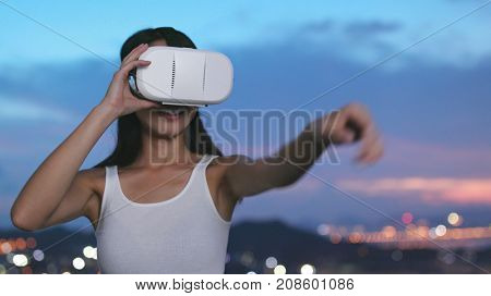 Woman watching with VR device in the evening