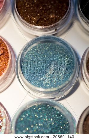Cosmetics. Pigments for make-up, eyes, lips, face and body. Brilliant radiant, scattered multicolored powders.