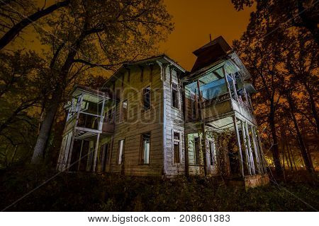 Old creepy wooden abandoned haunted mansion at night
