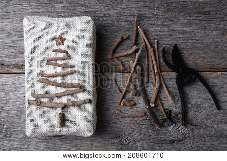 Overhead shot of a burlap wrapped Christmas present with a twig tree and star. Assorted twigs and pruning shears are also on the rustic wood table.