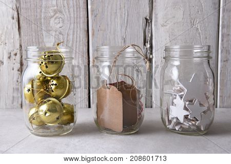 Christmas present wrapping supplies. Three mason jars with gift tags, wood stars, and sleigh bells against a rustic white wood wall.