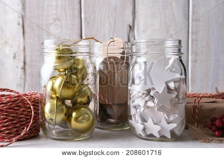 Christmas present wrapping supplies. Closeup of three mason jars with gift tags, wood stars, and sleigh bells against a rustic white wood wall.