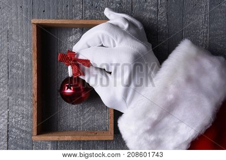 Santa Claus hanging a red jingle bell inside a wood frame on gray wood wall.