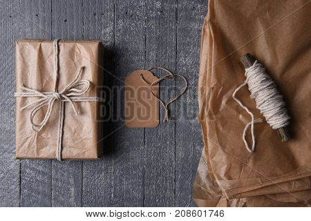 High angle shot of plain brown paper wrapped Christmas gift with blank tag and extra paper and string.