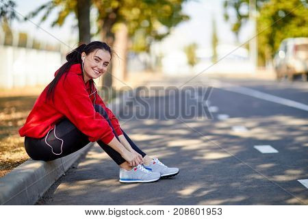 A young athletic girl in a red sweatshirt listens to music and corrects sneakers in the fresh air in the park on the barge.