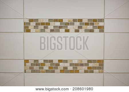 White tile with earth tone colored trim.