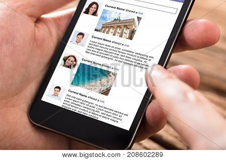 Close-up Of Person Using Mobile Phone For Surfing On Social Website