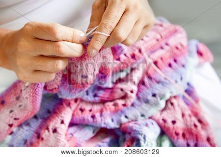 A Woman Knits With Knitting Needles A Lilac Sheet Made Of Thick Yarn
