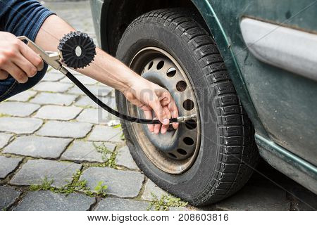 Person's Hand Measuring Car Tyre Pressure With Pressure Gauge Outdoors