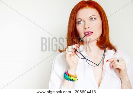 Red-haired Girl In A White Blouse And Black Glasses. Colorful And Bright Costume Jewelry.