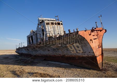 Aral sea disaster. Abandoned rusty fishing boat at the desert on the place of former Aral sea