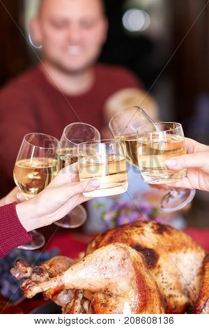 Happy family having dinner on the holiday table at home. Tasty baken chicken with vegetables on the table. Family drinking wine. Close-up of glasses with wine. Food concept.