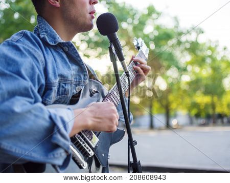 Handsome young man plays the guitar and sings songs in a group on the street in a park in a denim jacket on a blurred background. Close-up of man. Music concept.