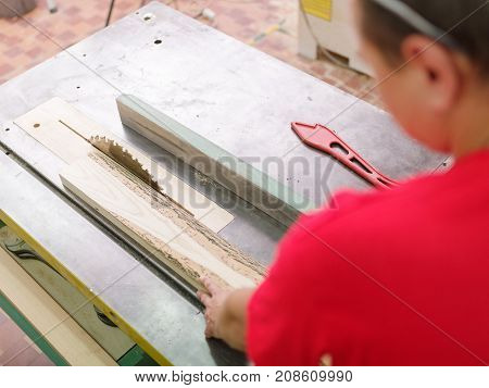 The carpenter in glasses and his form saws a timber beam on a circular saw in the working room