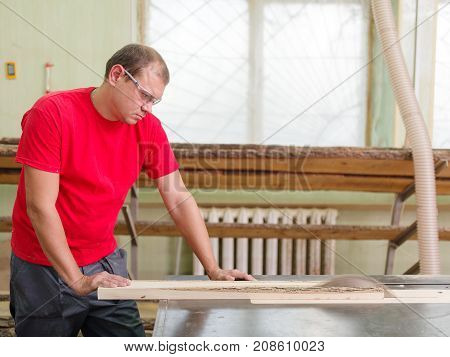 Joiner in profile saws a timber beam on a circular saw close-up in a working room