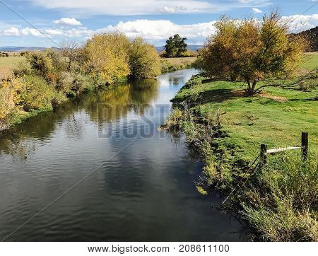 The Crooked River in Central Oregon winds through farmland with colorful trees and clouds reflecting off of its surface on a sunny fall day.