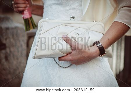 Beautiful wedding dress on a bride with white handbag and beautiful bouquet in hands