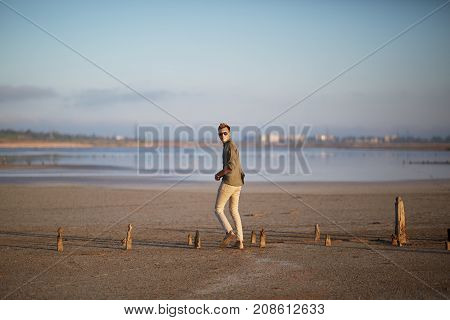 A young guy in white jeans, a shirt and glasses, on a sandy beach by the lake. Against the background of a blurry city. In full growth.