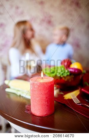 Happy family having dinner on the holiday table at home. Tasty baken chicken with vegetables on the table. Close-up of red candle. Food concept.