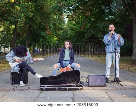 An excellent young men plays the guitar and sings songs in a group on the street in a park in a denim jacket on a blurred background. Full lenght of men.