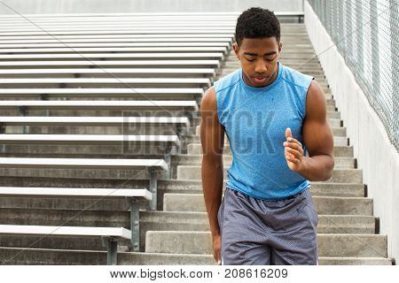 Young African Amerian teenage athlete running the bleachers.