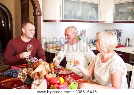 Happy family having dinner on the holiday table at home. Tasty baken chicken with vegetables on the table. Food concept.
