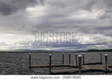Wide view of a small pier and weathered corner posts shot against Burlington Bay, Vermont with land in the distance on a cloudy gray late afternoon day in October.