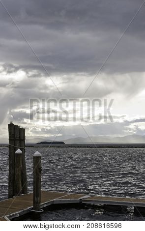 Vertical of a small pier and weathered corner posts shot against Burlington Bay, Vermont with land in the distance on a cloudy gray late afternoon day in October.