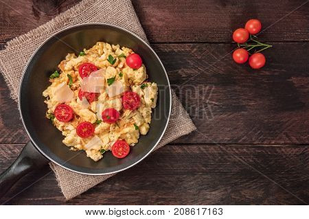 An overhead photo of a skillet of scrambled eggs with cherry tomatoes, fresh parsley, and grated cheese, shot from above on a dark rustic background texture, with a place for text