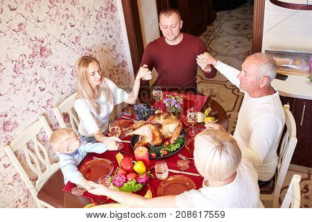 Happy family having dinner on the holiday table at home and thank God for food. Tasty baken chicken with vegetables on the table. Food concept.