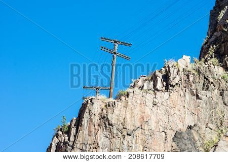 Some power lines and hydro poles on rock cliff face.