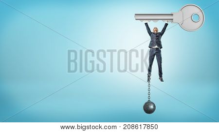 A businessman chained to an iron ball flies upwards while holding a huge metal key. Dreams and goals. Free yourself. Key to success.
