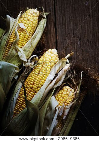 Aerial view of sweetcorn cob on wooden background