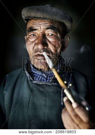 Mongolian man in traditional dress smoking a pipe.