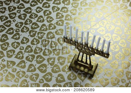Tiny brass Hanukkah menorah with white candles on a background of metallic gold leaves