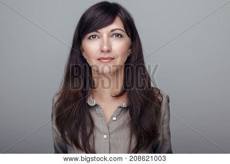 Closeup portrait of beautiful young middle age brunette Caucasian woman with brown eyes looking in camera. Girl female with long dark hair. Studio beauty shot.