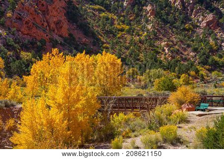 Gorgeous fall foliage, red rocks, bridge and park bench and the entrance of Cedar Breaks National Monument and Dixie Forest in Utah.