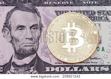 Golden cruptocurrency bitcoin on dollar banknote background. High resolution photo.
