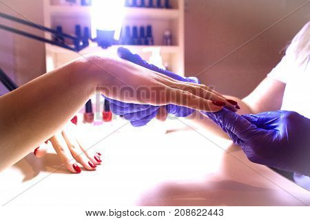 master of manicure paints nails to the girl in the salon