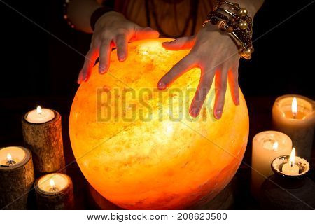 Shining Crystal Ball With Candles And Hands Of A Female Fortune Teller