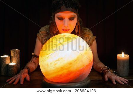 Young Psychic Is Telling The Future, Crystal Ball And Candles In Front Of Black Background