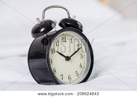 Black Alarm Clock At 8 Am On The Bed