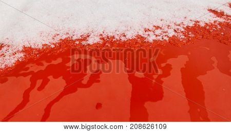 Abstract image of snow on a red background. Red and white. First snow.  White and red. Snow background. Snow on red metal surface.
