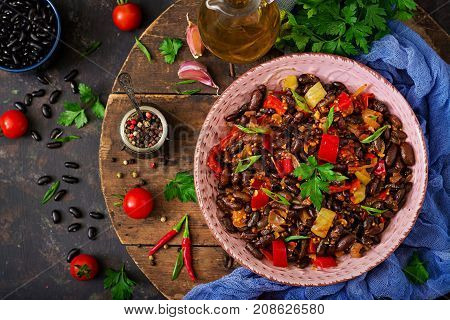 Stewed Black Beans With Sweet Peppers And Tomatoes With Spicy Sauce In A Pink Bowl