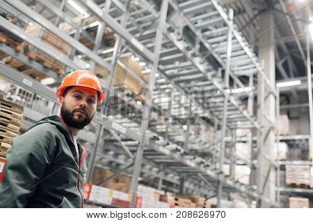 wholesale, logistic, people and export concept - manager or supervisor with tablet at warehouse. looking thoughtfully at the camera