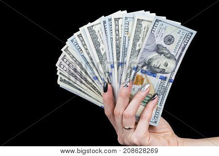 Hand with money isolated on black background. US Dollars in hand. Handful of money. Business woman offering money. Counting money. Hand holds a bundle of dollar bills. Financial Credit concept.