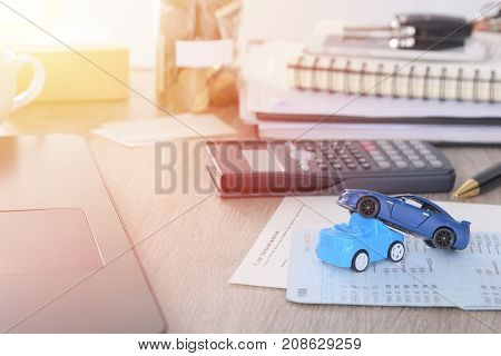 Car insurance concept:Car claim form with car toy crash on desk with money coin in jar bank.
