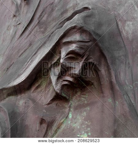 Detail of a mourning sculpture on a cemetery. (Religion faith suffering concept).